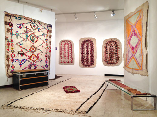 a very unusual rug from the Ourika valley on the left wall, an unusual minimal Beni Ouarain rug + a Boujad pillow on the floor, three turkmen felt prayer rugs on the back wall, another Afghan felt rug on the right wall