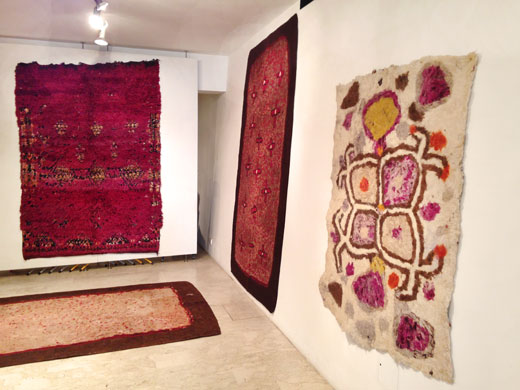 a deep purple Beni Mguild rug on the back wall, a double sided turkmen felt rug on the bottom + in the background on the right wall + another Afghan felt rug in the foreground