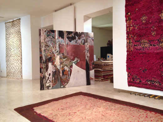 an very subtle Azilal rug in the background, a double sided turkmen felt on the floor, a deep purple Beni Mguild rug on the right wall + a painting by Michael Fanta in the center