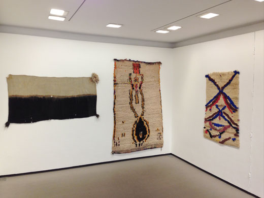 the Douglas Hyde Gallery, Dublin, Ireland: 'Textiles from the Atlas Mountains', a seemingly 'figurative' rug from Azilal (center), central High Atlas, a small saddle rug from the central Middle Atlas (right) + a highly rare women's veil from Ait Abdellah in the Anti-Atlas